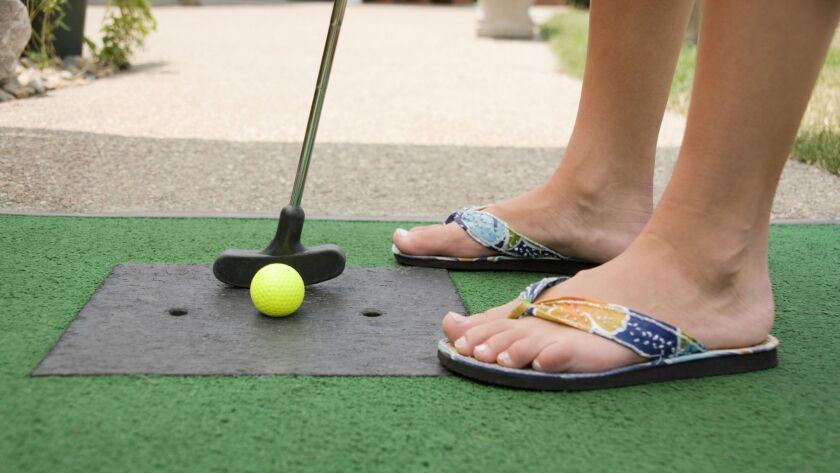 Close-up of person putting on miniature golf course