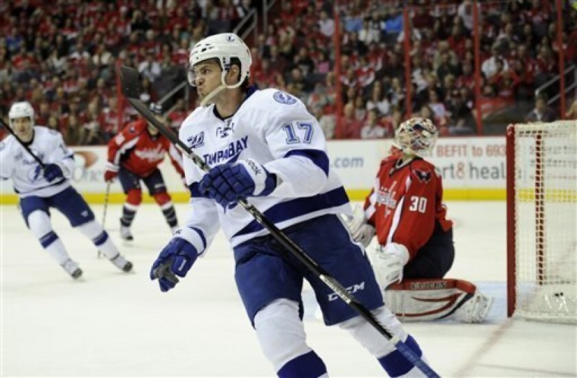 Tampa Bay Lightning center Alex Killorn (17) skates by Washington Capitals goalie Michal Neuvirth (30), of the Czech Republic, after he scored a goal during the second period of an NHL hockey game, Sunday, April 7, 2013, in Washington. (AP Photo/Nick Wass)