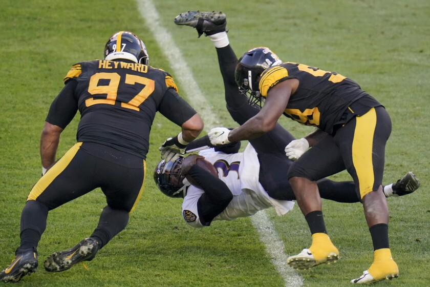 Baltimore Ravens quarterback Robert Griffin III (3) flies as he is tripped up as he scrambles past Pittsburgh Steelers defensive end Cameron Heyward (97) and inside linebacker Vince Williams (98) in the first half during an NFL football game, Wednesday, Dec. 2, 2020, in Pittsburgh. (AP Photo/Gene J. Puskar)