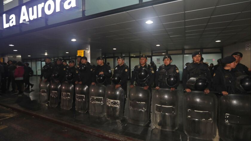 Anti-riot police stand guard at La Aurora International Airport in Guatemala City, where the Guatemalan government banned the entry Saturday of Yilen Osorio, an official with a U.N.-backed anti-corruption commission. After a court order, Osorio was released Sunday.