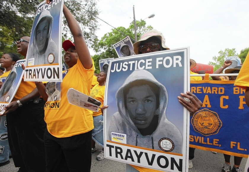 Protesters hold up signs in a march and rally for slain Florida teenager Trayvon Martin in Sanford, Fla., on March 31, 2012.