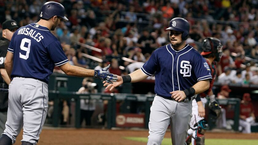 The Padres' Austin Hedges, right, is congratulated by teammate Adam Rosales (9) after scoring a run against the Arizona Diamondbacks during the seventh inning of a baseball game, Sunday, Oct. 2, 2016, in Phoenix.