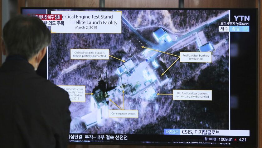 A man watches a TV screen showing an image of the Sohae Satellite Launching Station in Tongchang-ri,