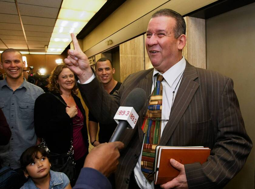 Former Bell City Council member Luis Artiga, right, points upward after being acquitted on all charges in the Bell corruption trial. With him, from left, are his son Joshua, daughter Sarah Marie, wife Miriam and son Christian.