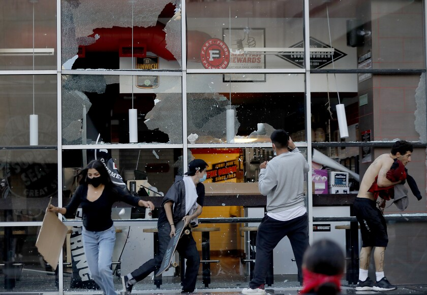 Protesters smash windows along Figueroa Street in downtown Los Angeles on Saturday.