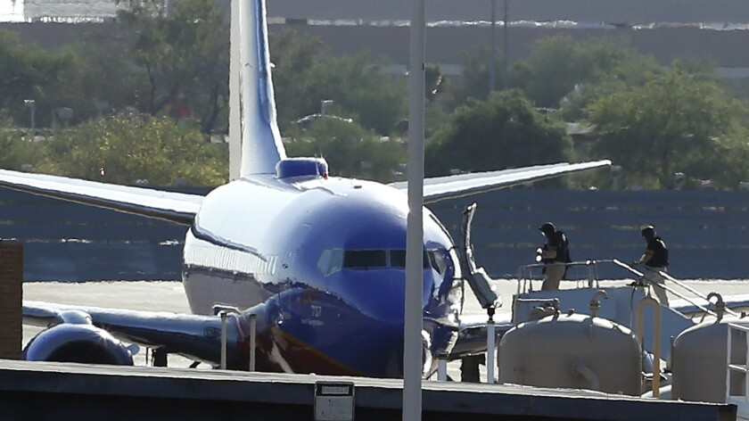 Members of a bomb squad enter a Southwest Airlines plane at Phoenix Sky Harbor International Airport after a phoned-in bomb threat against the flight from Los Angeles to Austin, Texas, led to the plane being diverted Monday afternoon.