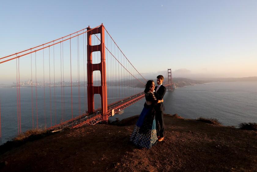 The newlyweds Tulika Jha and Mike Borden enjoy the sunset next to the Golden Gate Bridge.
