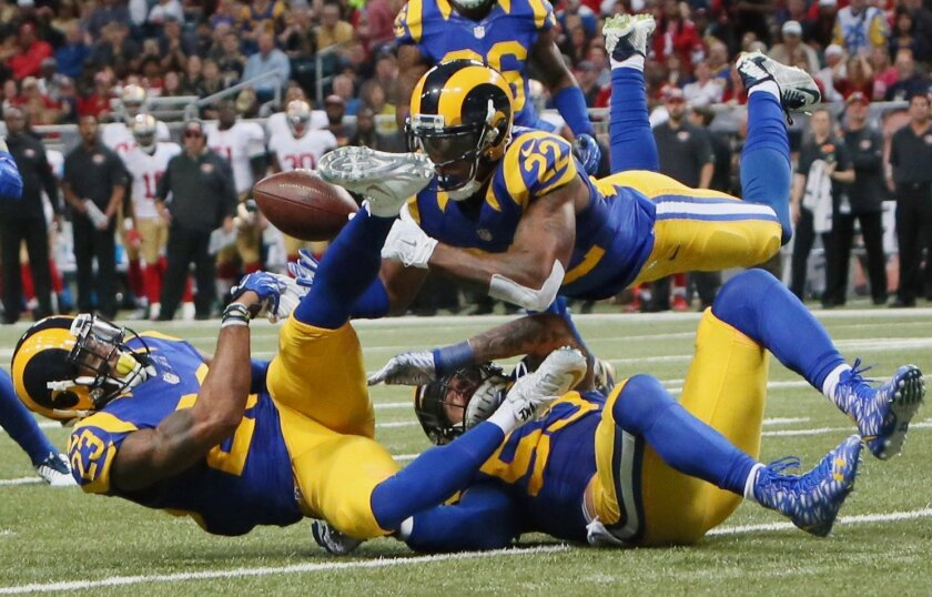 St. Louis Rams' Rodney McLeod, cornerback Trumaine Johnson (22) and linebacker James Laurinaitis converge on a pass but are unable to make an interception during an NFL football game against the San Francisco 49ers Sunday, Nov. 1, 2015, in St. Louis. (Chris Lee/St. Louis Post-Dispatch via AP)  EDWA