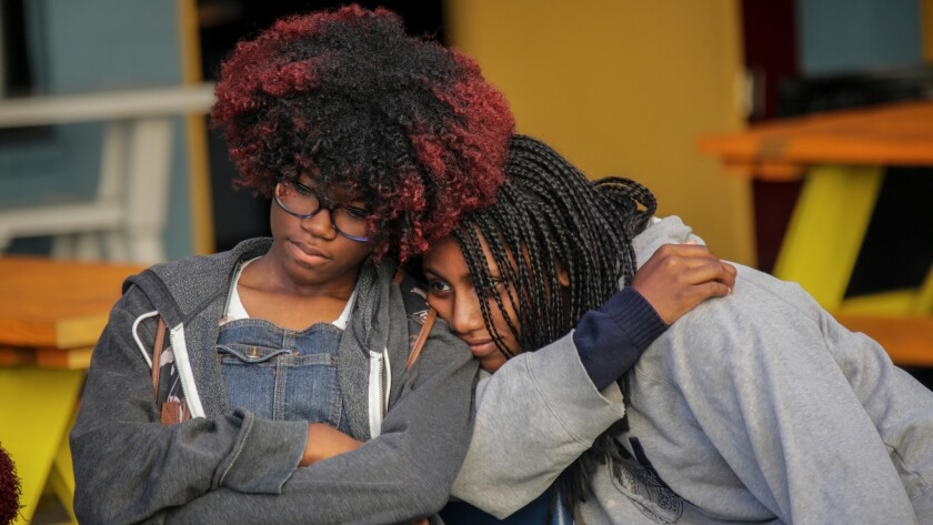Students Zoe Miles, 14, left, and Pearl Green, 15, appear somber as they mark the last day at City High School.