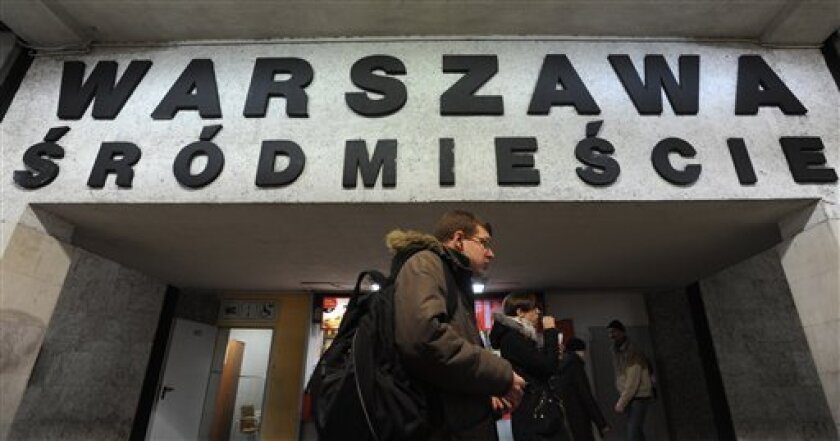 People walk under a board with the name of a train station with several Polish diacritical marks, in Warsaw, Poland, Thursday, Feb. 21, 2013. Polish language experts have launched a campaign, as part of the UNESCO International Mother Language Day, to preserve the challenging system of its diacriti