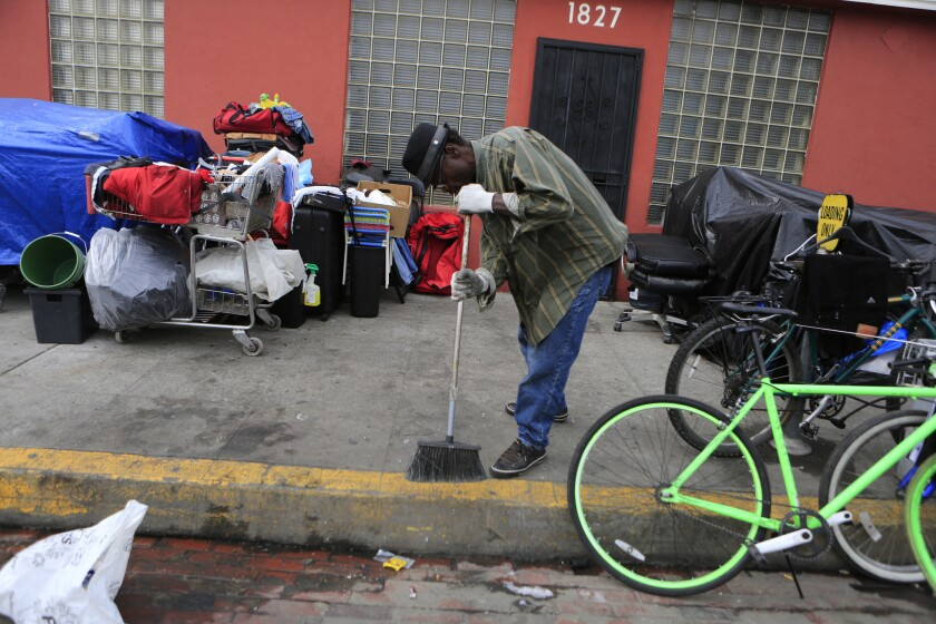 Roy Carter, a 57-year-old homeless man, sweeps the sidewalk where his belongings are gathered on South Hope Street in January. Over the last two years, hundreds of street encampments have jumped their historic borders in downtown Los Angeles, lining the 110 Freeway and filling underpasses from Echo Park to South Los Angeles.