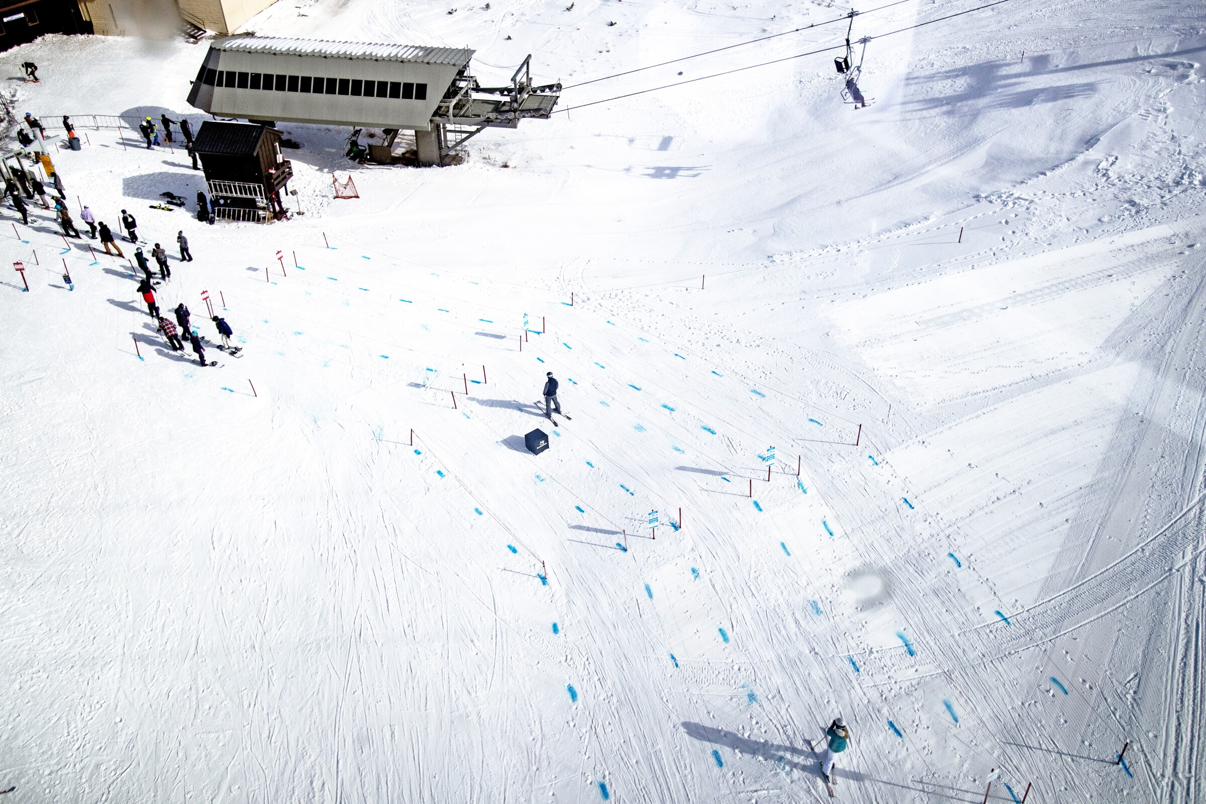 Blue dye in the snow at Mammoth Mountain marks physical distancing.
