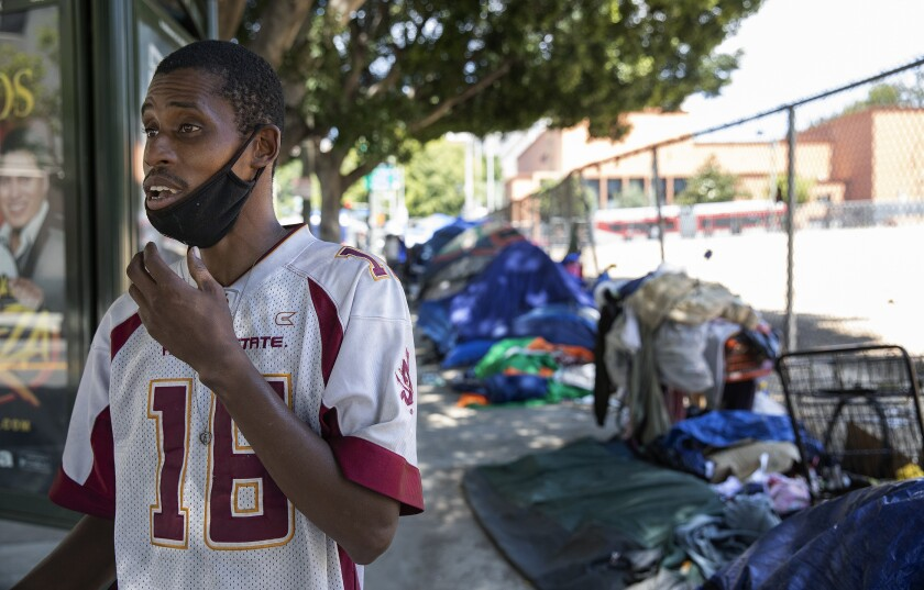 Karl Hamilton stands outside his tent in downtown Los Angeles