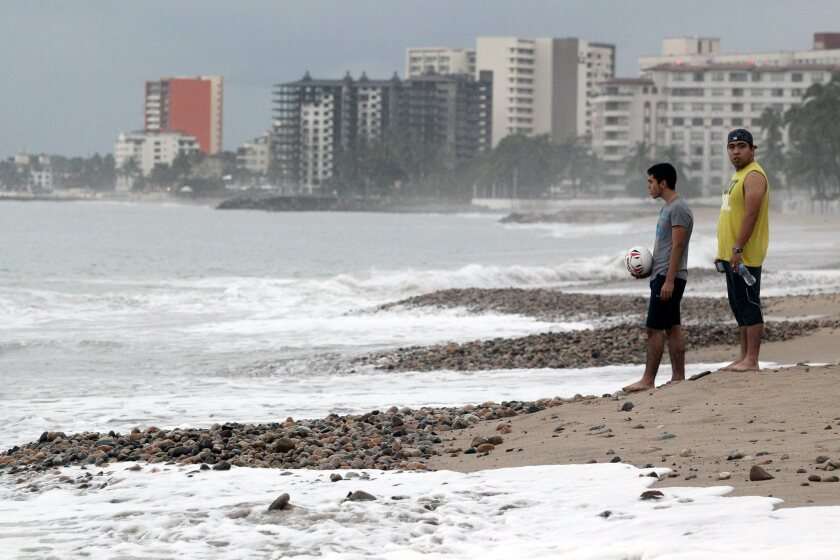 Two men visit a beach Saturday in Puerto Vallarta, Mexico, the day after Hurricane Patricia hit the country's West Coast. The resort town was unscathed by the powerful storm.