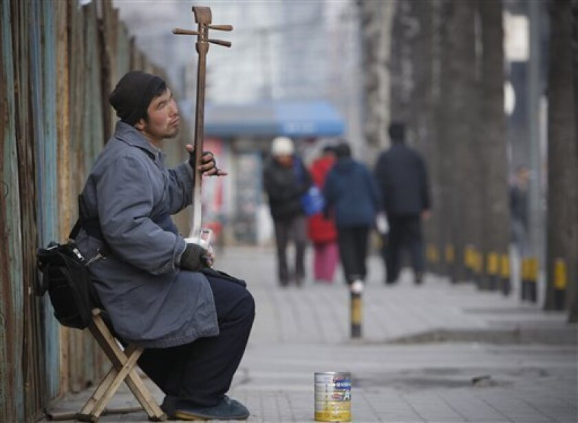 A Chinese blind beggar performs along a sideway in downtown Beijing, Monday, Feb. 1, 2010. (AP Photo/Vincent Thian)