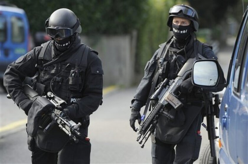 Swiss special police arrive on Thursday, Sept. 9, 2010, outside a house in Biel, Switzerland, where a 67-year-old man holed himself up since Wednesday and has fired several shots. Police say one officer has been badly injured in a standoff with the gunman in the western city. (AP Photo/Keystone, Lukas Lehmann)