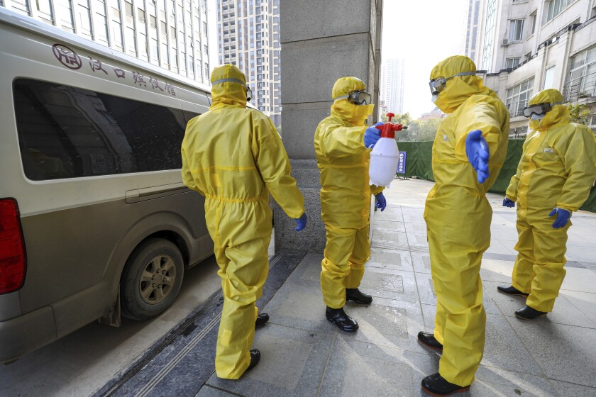 Funeral workers disinfect themselves after handling a coronavirus victim in Wuhan, China.