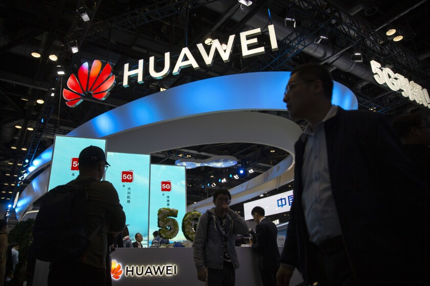 FILE - In this Oct. 31, 2019, file photo, attendees walk past a display for 5G services from Chinese technology firm Huawei at the PT Expo in Beijing. A federal appeals court refused Friday, June 18, 2021 to hear Chinese tech giant Huawei's request to throw out a rule used to bar rural phone carriers on national security grounds from using government funds to purchase its equipment. (AP Photo/Mark Schiefelbein, File)
