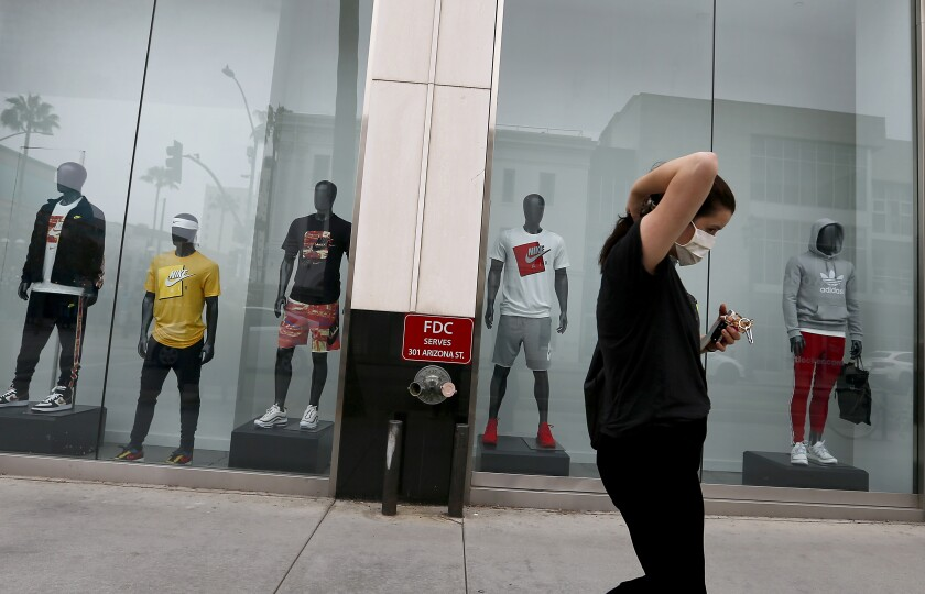 A woman walks by a shuttered luxury retail store in Santa Monica.