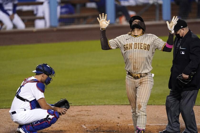 Fernando Tatis Jr. (centro), de los Padres de San Diego, celebra un jonrón solitario mientras el catcher de los Dodgers
