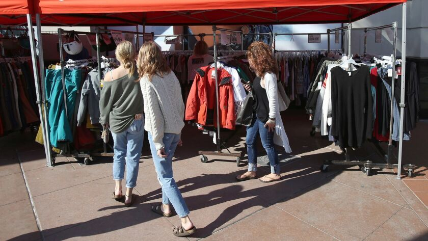 Shoppers walk through racks of Jack's merchandise in downtown Huntington Beach. The Huntington Beach