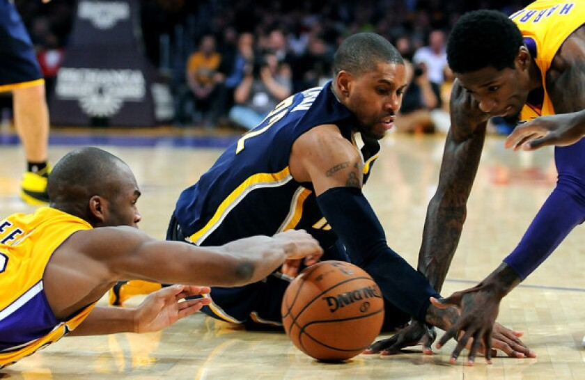 Lakers teammates Jodie Meeks, left, and Manny Harris, right, battle Indiana Pacers point guard C.J. Watson for a loose ball during the first half of Tuesday's game at Staples Center.