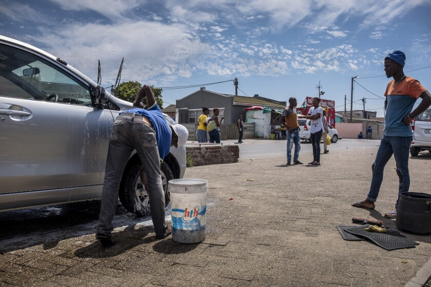 Akena Dubanga, who owns a car wash in Gugulethu, about 10 miles from Cape Town, South Africa, says it now uses buckets rather than hoses to use less water per car. Workers are shown Feb. 14, 2018.