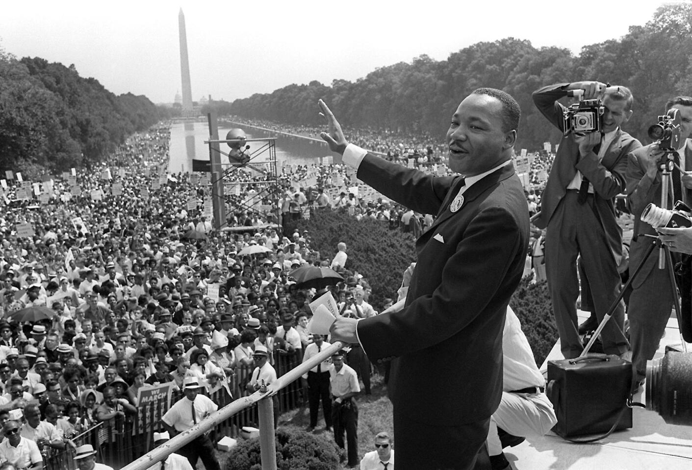 Civil rights leader Martin Luther King Jr. waves to supporters from the steps of the Lincoln Memorial on the Mall in Washington, D.C.