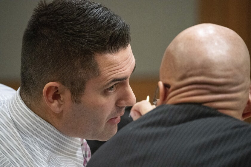 In this photo taken Tuesday, Dec. 3, 2019, dentist Seth Lookhart talks with his lawyer Paul Stockler during his trial in Anchorage, Alaska. The Alaska dentist is accused of fraud and unnecessarily sedating patients and also performing a procedure while riding a wheeled, motorized vehicle known as a hoverboard, authorities said. Prosecutors charged 34-year-old Seth Lookhart with felony Medicaid fraud and reckless endangerment. (Loren Holmes/Anchorage Daily News via AP)