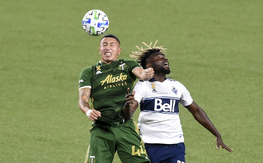 Portland Timbers midfielder Marvin Loria, left, and Vancouver Whitecaps midfielder Leonard Owusu compete for the ball during the first half of an MLS soccer match in Portland, Ore., Sunday, Sept. 27, 2020. (AP Photo/Steve Dykes)