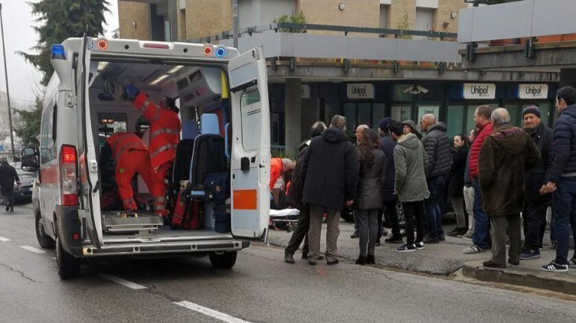 Paramedics, background center, attend a wounded man after a shooting broke out in Macerata, Italy, S