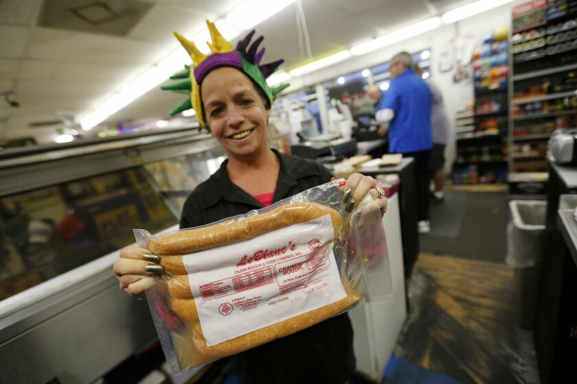 Jeanne Marie Sewell holds a package of Le Blanc's Boudin at the Sav N' Time convenience store and gas station in Harahan, La., Tuesday, Jan. 26, 2016. Boudin is a tradition that dates back to the 1700s, when French Canadians came to Louisiana. Robert Carriker, a professor of history at the University of Louisiana in Lafayette, says Cajuns started using local ingredients and spices to make sausages that are different from Old World recipes. (AP Photo/Gerald Herbert)