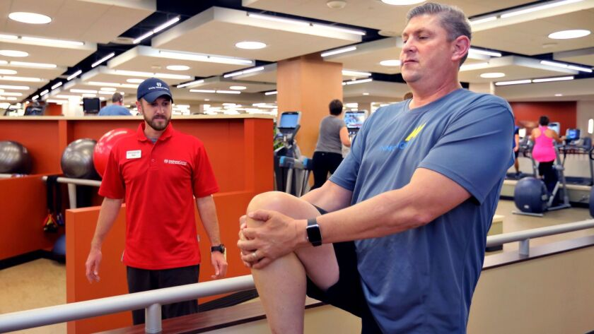 """Cancer survivor Keith Stuessi, 50, stretches during an evening workout with Tri-City Medical Center's """"Lucky 13"""" at the Tri-City Wellness Center in Carlsbad. At left is the group's coordinator and personal trainer Paul Carey."""