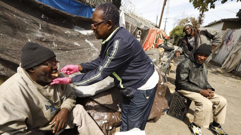 Rose Rios, 70, of Cover the Homeless Ministry, center, gives pie to Donald Shields, 59, who is legally blind and living in an alley in South Los Angeles.