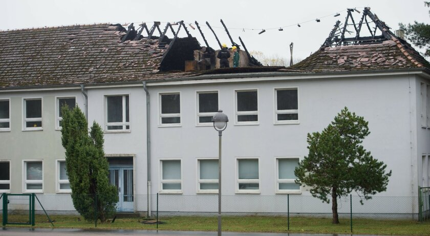 Police investigate after a fire in a planned refugee accommodation in Trassenheide on the Baltic Sea island of Usedom, Germany, Sunday Nov. 15, 2015. Police said hat the former office building of a metal construction company in Trassenheide went up in flames for reasons that are still unknown. (Stefan Sauer /dpa via AP)