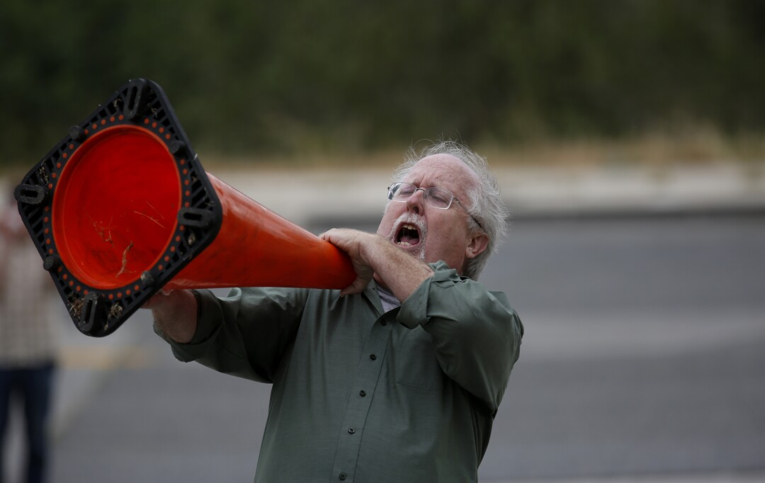 A man chants along with dozens of protesters at the Aliso Canyon storage facility in 2016.