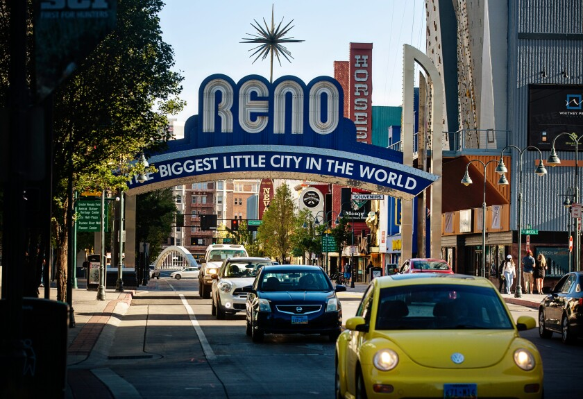 Cars and pedestrians pass by the Reno Arch, an iconic landmark that spans Virginia Street in downtown Reno.