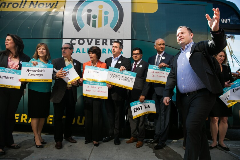 Covered California Executive Director Peter V. Lee, center, gathers with local lawmakers at an open enrollment event in 2015.