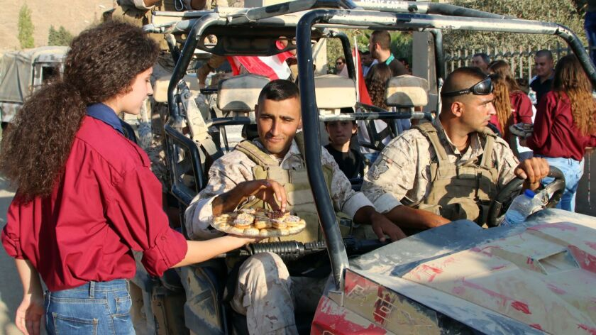 A young woman serves pastries to Lebanese army soldiers in the eastern town of Ras Baalbek, Lebanon
