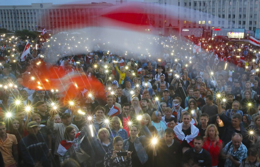 FILE - In this Wednesday, Aug. 19, 2020 file photo, Belarusian opposition supporters light phones lights and wave an old Belarusian national flags during a protest rally in front of the government building at Independent Square in Minsk, Belarus. Belarus President Alexander Lukashenko has relied on massive arrests and intimidation tactics to hold on to power despite nearly three months of protests sparked by his re-election to a sixth term, but continuing protests have cast an unprecedented challenge to his 26-year rule. (AP Photo/Dmitri Lovetsky, File)