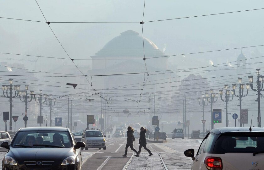 People walk in the streets of polluted Turin, Italy, on Dec. 19, 2015.