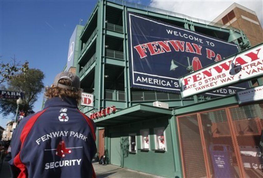 A security guard keeps an eye on things outside Gate D at Fenway Park in Boston, Tuesday, Oct. 29, 2013. If the Boston Red Sox are able to win the baseball World Series at at the stadium, police and city officials want to make sure fans celebrate responsibly. Boston holds a 3-2 lead over the St. Louis Cardinals with Game 6 and if necessary Game 7 scheduled at Fenway for Wednesday and Thursday nights. Police plan to put extra patrols on duty to guard against any unruly celebrations. (AP Photo/Eli