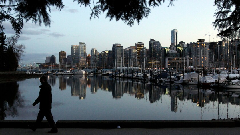 A man walks through Stanley Park as the Vancouver skyline is reflected in the water behind him on Feb. 5, 2010, one week before the start of the Vancouver 2010 Olympic Games.