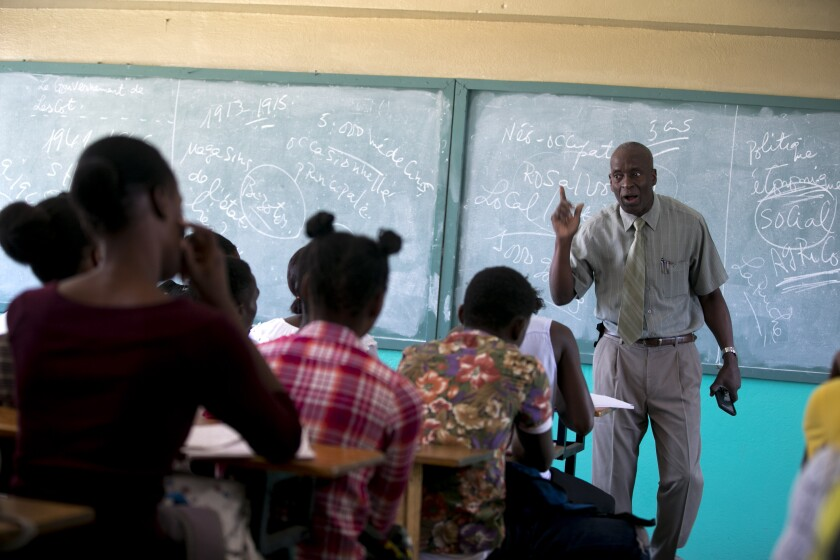 Students listen to school Director Jean Marc Charles at the Lycée school, which reopened about a week earlier than other schools in Petion-Ville, Haiti, Thursday, Nov. 28, 2019. Some Haitian children have begun to return to school after classes halted during months of violent unrest. (AP Photo/Dieu Nalio Chery)