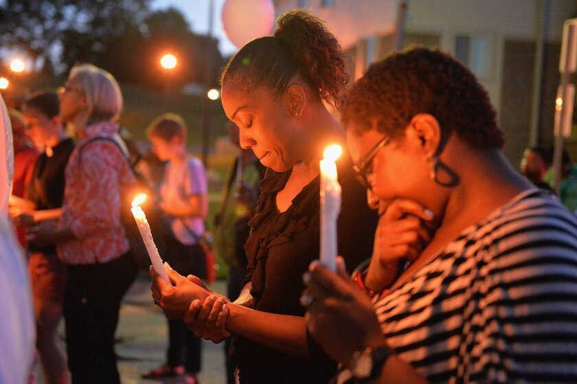 Mourners pause for prayer during a vigil for Jamyla Bolden on Thursday in Ferguson, Mo. Jamyla, 9, was hit and killed by a stray bullet as she was doing homework on her mother's bed.