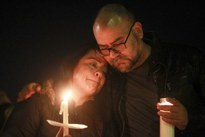 Ruben Gala and Jessica Rosario, both cousins of Sabrina Rosario, who was killed along with her four sons in a domestic murder-suicide last weekend, embrace during a candlelight vigil at the Paradise Hills United Church of Christ on Nov. 22.