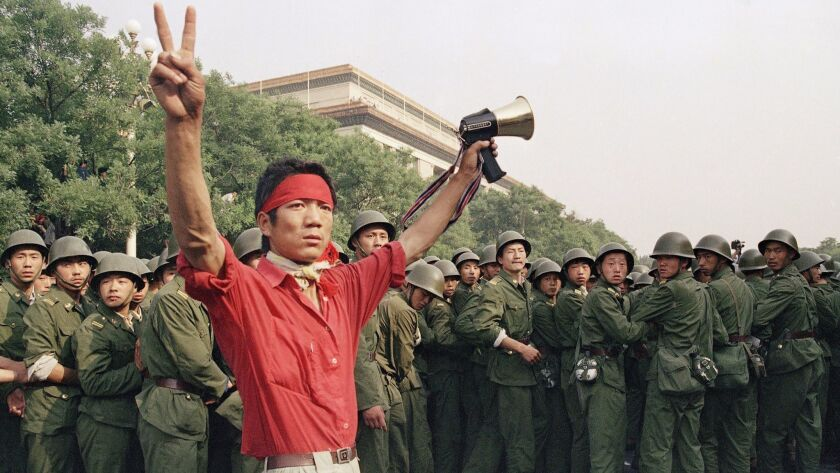 FILE - In this early June 4, 1989, file photo, civilians hold rocks as they stand on a government ar
