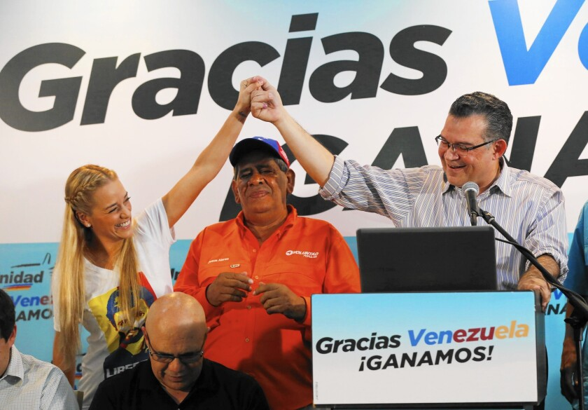 Lilian Tintori, wife of jailed opposition leader Leopoldo Lopez, joins reelected opposition lawmaker Enrique Marquez at a news conference in Caracas, Venezuela.
