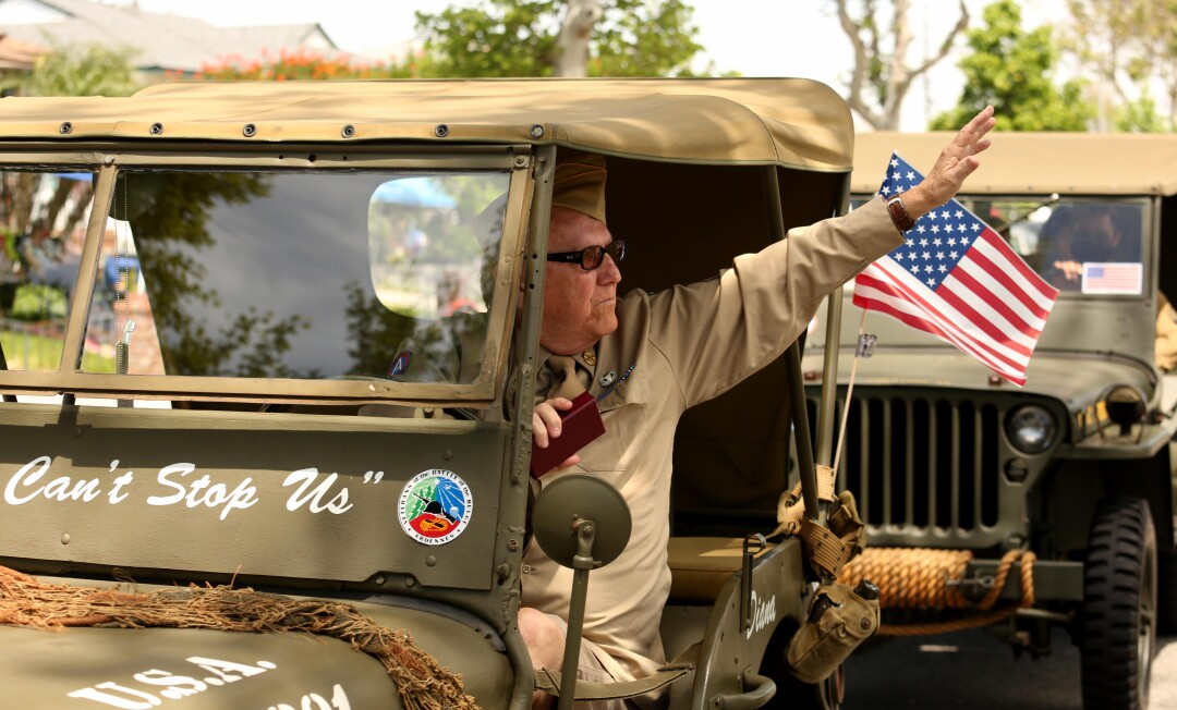 A veteran waves to World War II veteran Lt. Col. Sam Sachs during a birthday parade in Lakewood on April 26.