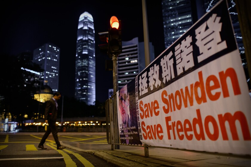 A man crosses a street next to banner displayed in support of former U.S. National Security Agency contractor Edward Snowden in Hong Kong.